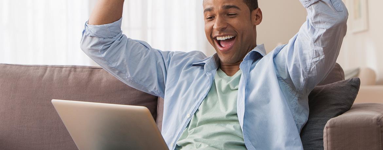 Man cheering at his computer screen.