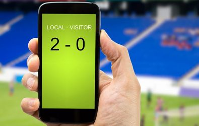 Hand holding a mobile phone displaying a football score, with a stadium in the background