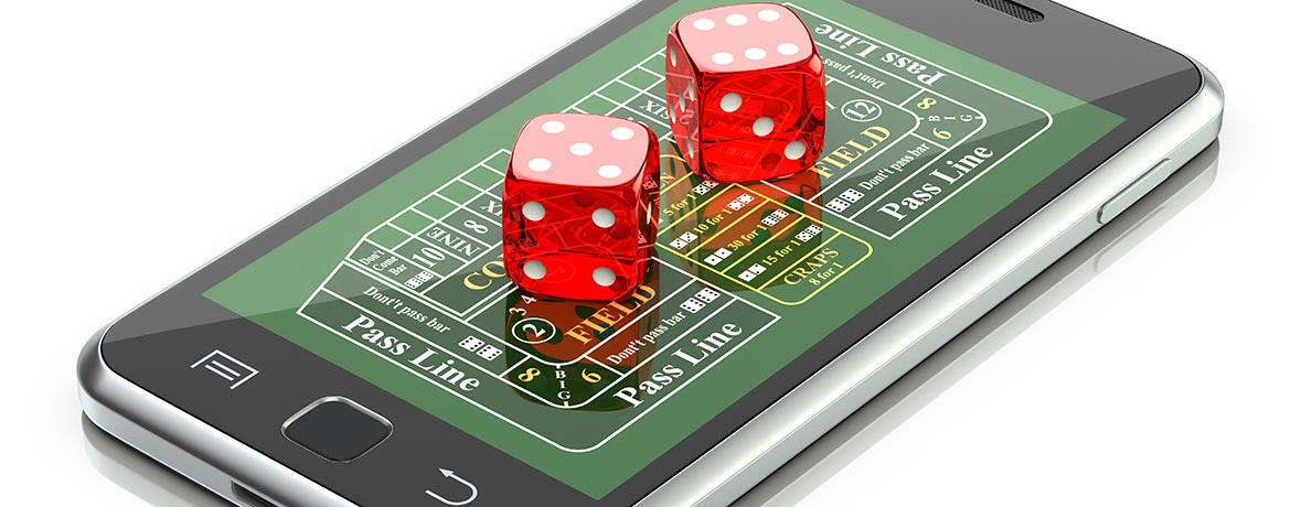Dice sitting on top of a mobile phone displaying a craps board