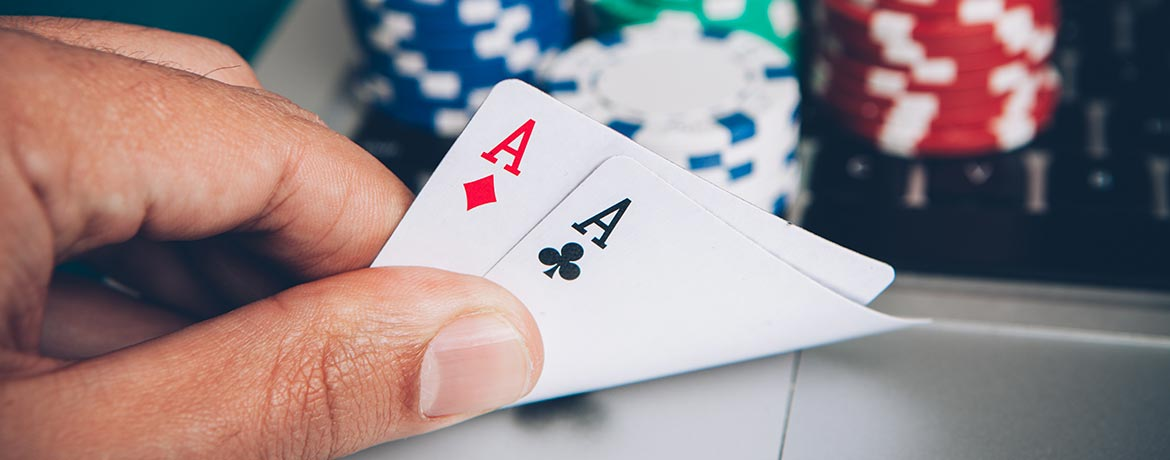 A hand holding two aces